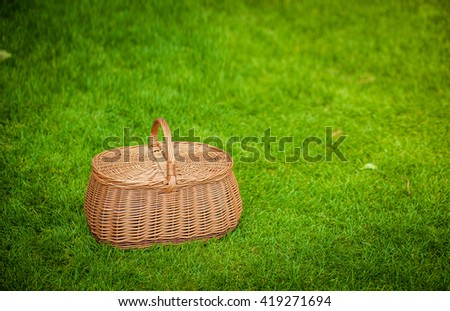 Wicker Picnic Basket On The Fresh Summer Grass . Weekend Resting Concept - stock photo