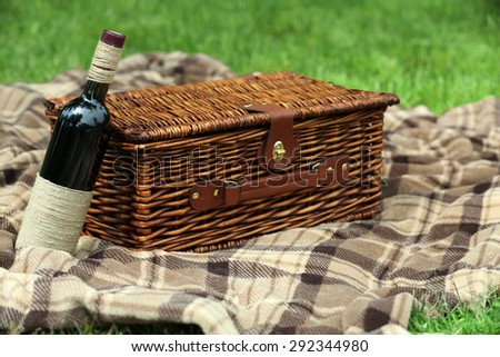 Wicker picnic basket, wine bottle and plaid on green grass, outdoors  - stock photo