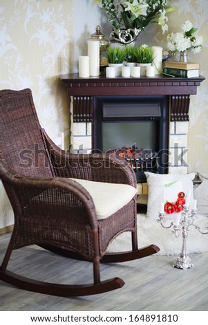 Wicker rocking chair, candlestick and fireplace with candles and flowers in cosy room.  - stock photo