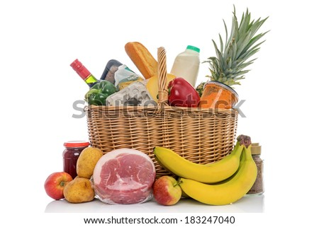 Wicker shopping basket full of groceries including fresh fruit, vegetables, meat and dairy products. Isolated on a white background. - stock photo