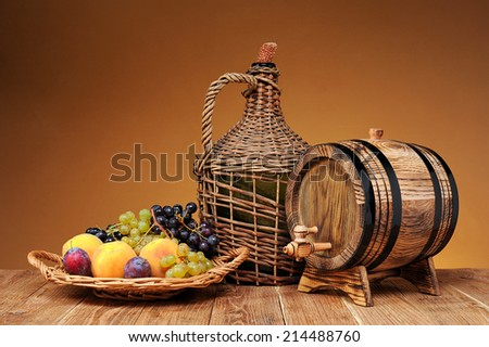 Wicker wine bottle, grapes and wooden barrel on the table - stock photo