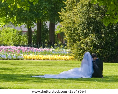 wide and groom sitting in the park