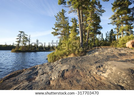 Wide angle afternoon shot of a rocky shore with pine trees on a Boundary Waters Canoe Area Wilderness lake in northern Minnesota - stock photo
