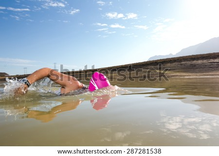 Wide angle close up image of a female triathlete swimming in a dam - stock photo
