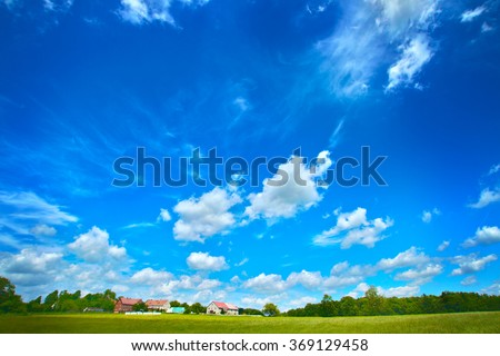 Wide angle clouds over green meadow with hoses on a farm under blue sky - stock photo