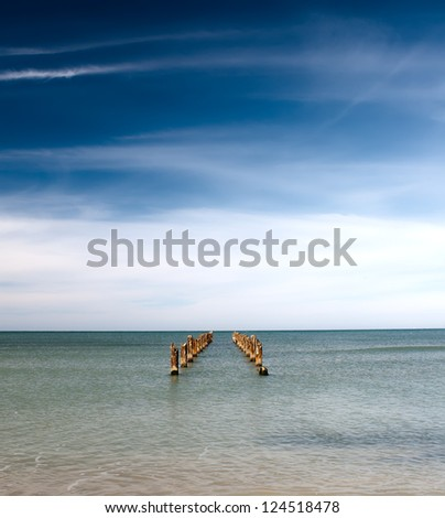 wide angle image of a ruined pier extending to the horizon. - stock photo