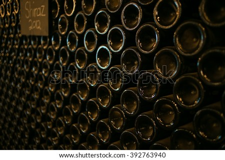 Wide angle image of a stack of wine bottles in an old dark wine cellar. Natural available light only. - stock photo