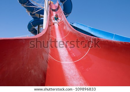 Wide angle image of little girl slid a big water slide down
