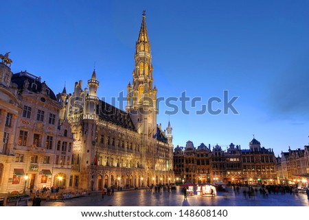Wide angle night scene of the Grand Place, the focal point of Brussels, Belgium. The Town Hall (Hotel de Ville) is dominating the composition with its 96m tall spire. - stock photo
