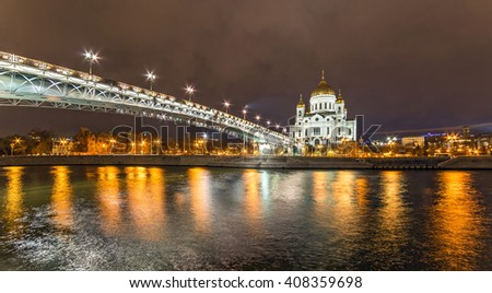 Wide angle night view of illuminated orthodox church, white bridge and river reflections in Moscow