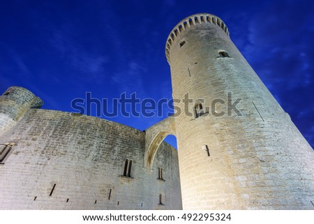 Wide angle of Bellver Castle tower against deep blue cloudy sky at sunset in Majorca, Spain