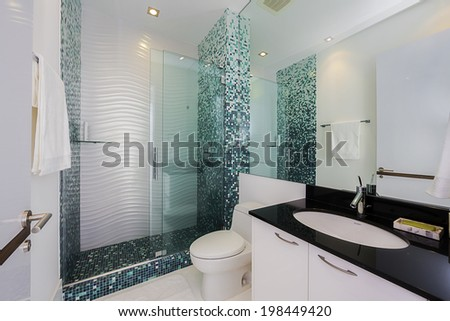 Wide angle of Modern Bathroom in turquoise with glass shower and black counter tops. - stock photo