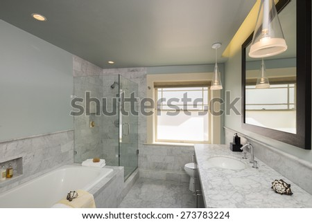 Wide angle of modern bathroom in white with Marble counter tops and all new appliances including glass shower. - stock photo