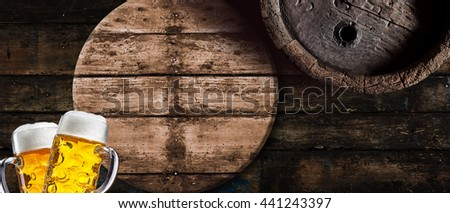 Wide angle Oktoberfest concept with two glass tankards of golden frothy lager against a background of old rustic vintage beer barrels with copy space