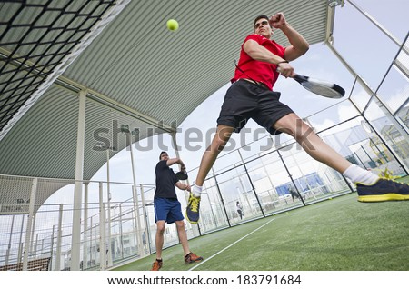 Wide angle paddle tennis couple smashing ball in court - stock photo
