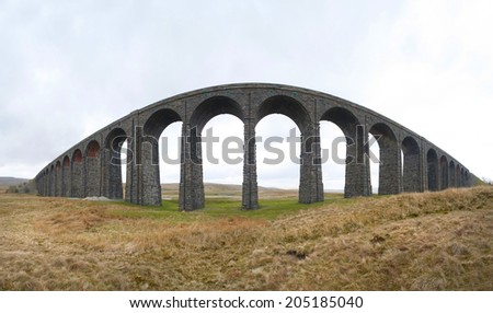 Wide angle panoramic view of the old stone arches of the Victorian railway viaduct over the River Ribble known as the Ribblehead Viaduct, North Yorkshire - stock photo