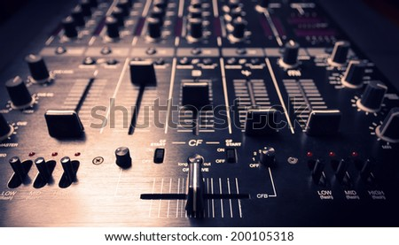 Wide angle photo of black sound mixer controller with knobs and sliders - stock photo