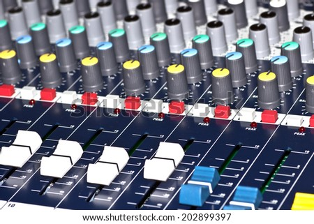 Wide angle photo of black sound mixer controller with knobs and sliders.