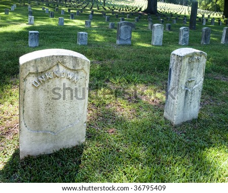 Wide angle photograph of a Civil War cemetery with an unknown tombstone in the foreground.