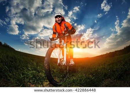 wide angle portrait against blue sky of mountain biker Cyclist - stock photo