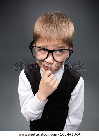 Wide angle portrait of little businessmen in spectacles, on grey background. Concept of leadership and success