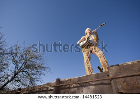 Wide angle shot of a banjo player against the blue sky