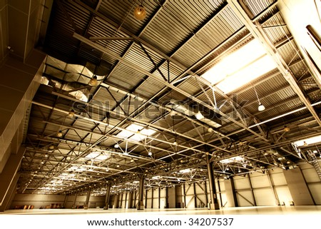 Wide angle shot of empty warehouse sepia toned - stock photo