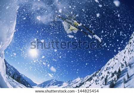 Wide angle shot of skier jumping from mountain ledge against sky - stock photo