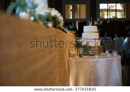 Wide angle shot of wedding cake at wedding reception head table - stock photo