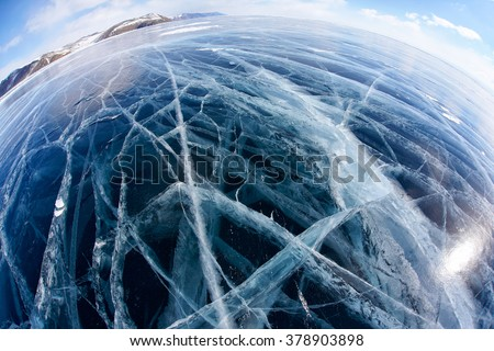 Wide angle shot with fisheye lens of winter ice landscape on Siberian lake Baikal with dramatic weather clouds on blue sky background
