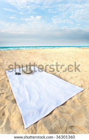 Wide angle towel on the beach, with hat and sunglasses. - stock photo
