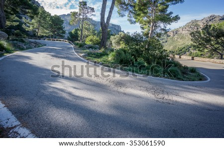 Wide angle view mountain with U-shape curved road - stock photo