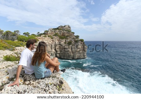 Wide angle view of a couple sitting in a cliff watching an ocean landscape in Mallorca - stock photo