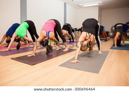 Wide angle view of a large group of people in a real yoga class doing the revolved down dog pose - stock photo