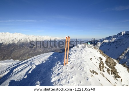 Wide angle view of a pair of back country ski on the top of the mountain in a clear bright day and scenic winter background