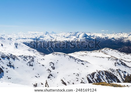 Wide angle view of a ski resort in the distance with elegant mountain peaks arising from the alpine arc in late winter season and beginning of spring. Torino Province on Italy France border. - stock photo