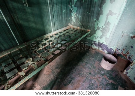 wide angle view of an old prison bed - stock photo