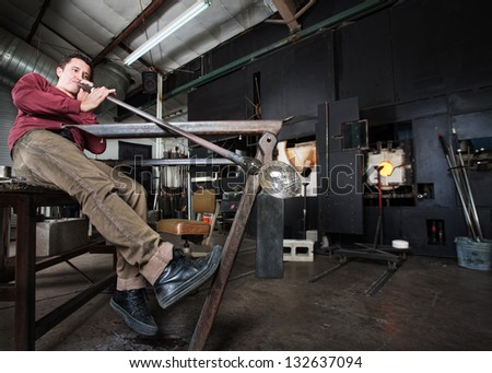 Wide angle view of artisan blowing into fine art glass - stock photo