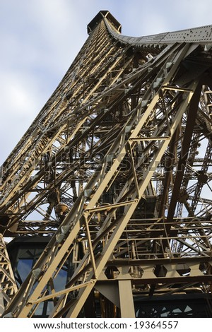 Wide angle view of Eiffel Tower, Paris, France, from below showing details of iron structure against blue sky