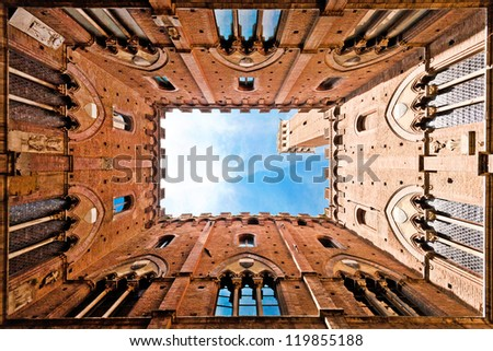 Wide angle view of famous Torre del Mangia at Palazzo Pubblico in Siena, Tuscany, Italy - stock photo