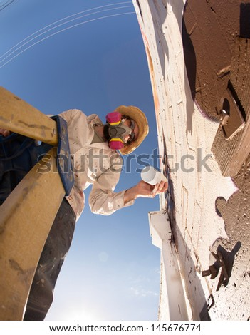 Wide angle view of graffiti artist on ladder making a mural