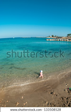 Wide angle view of little Caucasian child playing on sandy beach of Mediterranean sea, Cyprus