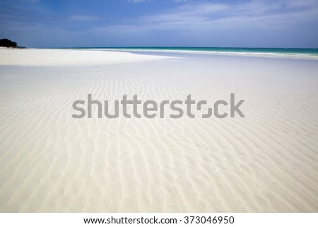 Wide angle view of rippled white sand beach covered with clear waters of the Indian Ocean. Blue sky with clouds. Diani Beach, Kenya. - stock photo