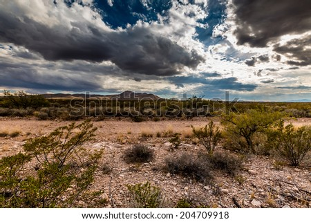 Wide Angle View of the Deserts of Western Texas with Rocky Hills and Storm Clouds in the Background. - stock photo