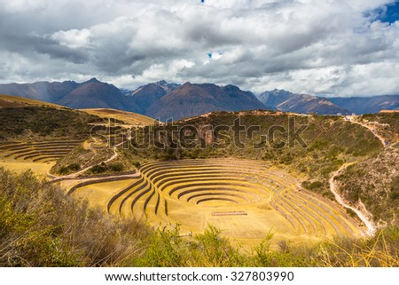 Wide angle view of the glowing majestic concentric terraces of Moray, supposed Inca's laboratory in Sacred Valley, major travel destination in Cusco region, Peru. Dramatic cloudy sky. - stock photo