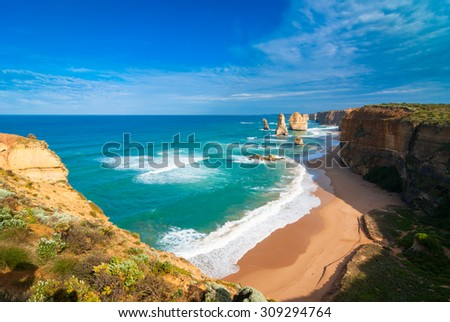 Wide angle view of the landmark Twelve Apostles along the Great Ocean Road in Victoria, Australia, with a sandy beach at the base of the cliffs in the foreground - stock photo