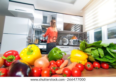 Wide angle view of young Woman cooking at the kitchen making healthy food with vegetables. Focus on vegetables. - stock photo