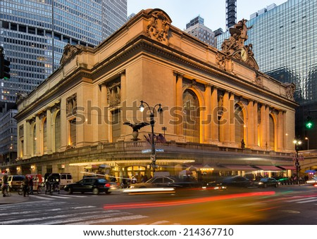 Wide angle view on the illuminated Grand Central Terminal at dusk during twilight with light trails on the streets representing the huge amounts of traffic in and around the station, in New York, USA - stock photo