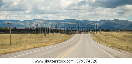 Wide asphalt mountain road in the sunny autumn somewhere in the USA - stock photo