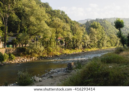 wide blue mountains river in small Ukrainian village in summer - stock photo